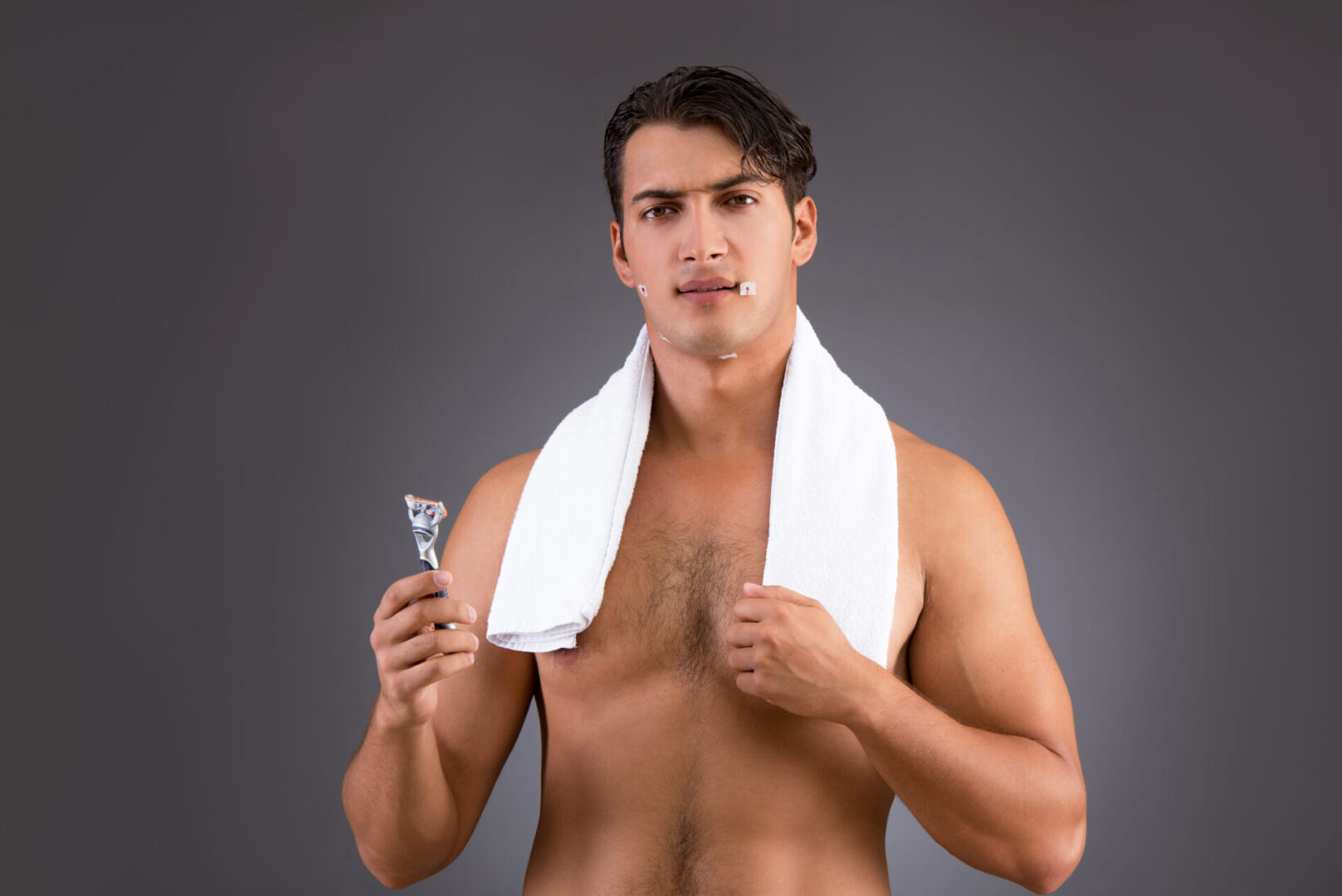 Handsome man shaving against dark background